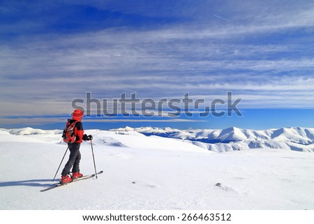 Ski mountaineer isolated on snow covered plateau surrounded by mountains - stock photo