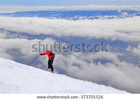 Ski mountaineer on a mountain side above the clouds - stock photo