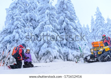 Ski patrol helping woman with broken arm rescue quad - stock photo