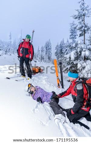 Ski patrol helping woman with broken leg lying in snow - stock photo