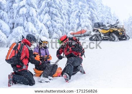 Ski patrol team rescue woman skier with broken arm - stock photo