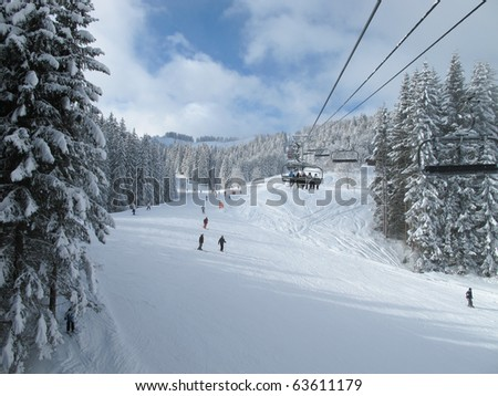 Ski piste and chair lift with snow covered trees on sunny day. Combloux ski area, French alps - stock photo