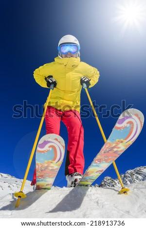 Ski, skier, sun and winter fun - woman enjoying ski vacation - stock photo