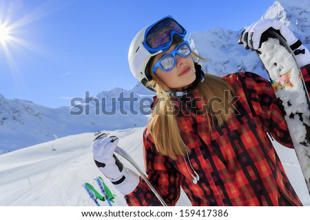 Ski, skier, sun and winter fun - young woman enjoying ski vacation - stock photo