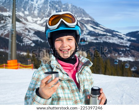 Ski, skier, winter. Lovely girl has a fun on ski - resting and drinking tea from a thermos. - stock photo