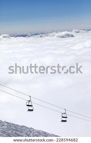 Ski slope, chair-lift and mountains under clouds. Caucasus Mountains, Georgia. Ski resort  Gudauri. - stock photo