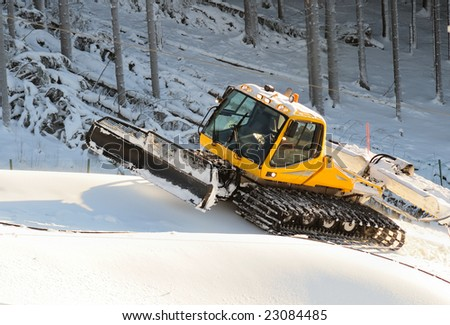 Ski slope with a yellow ratrak doing track maintenance