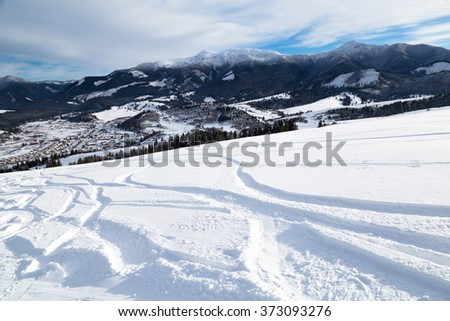 Ski slope with ski tracks - beautiful winter day - view from the mountain top to the valley - stock photo