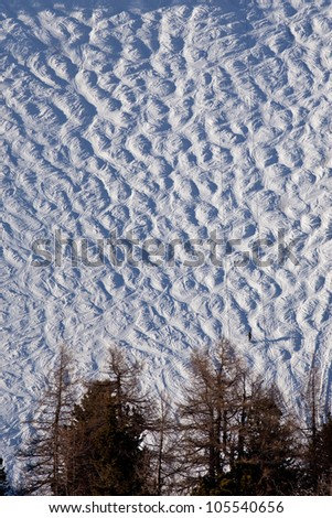 Ski slope with snowy bumps - stock photo