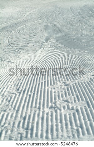 ski track and the footsteps on the groomed piste - stock photo