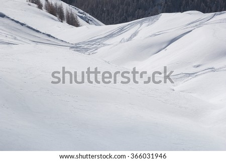 Ski tracks  on the background of snowy mountains and blue sky. Off-piste skiing in soft snow on a cold sunny day - stock photo
