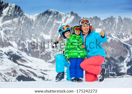 Ski, winter, snow, skiers, sun and fun - family photographed on phone during winter vacations.