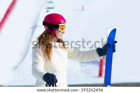 ski woman in winter snow with equipment helmet goggles poles profile side view - stock photo