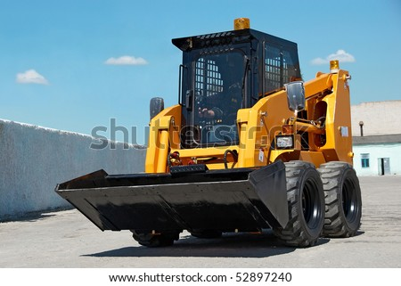 skid steer loader construction machine with bucket outdoors - stock photo