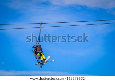 Skier and snowboarder sitting in ski lift in high mountains. Blue sky background. Place you text. - stock photo