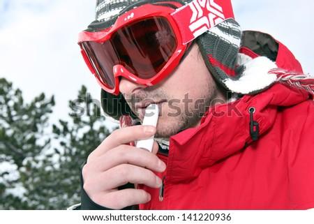 Skier applying lip balm - stock photo