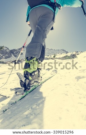 Skier ascending a slope. Ski touring where skier is tackling a steep slope. - stock photo