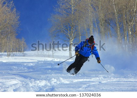 Skier charging down a slope in the Utah mountains, USA. - stock photo
