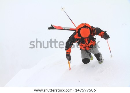 Skier climbing a snowy mountain in bad weather - stock photo
