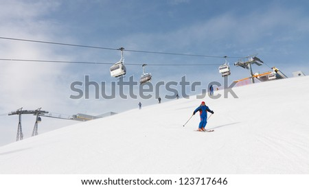 Skier cruising down the mountain near the summit of Kronplatz Ski Resort, South Tyrol, Italy. - stock photo