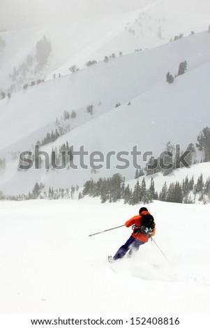 Skier dropping into a big bowl, Utah, USA. - stock photo