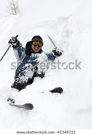Skier falling over in deep fresh snow - stock photo
