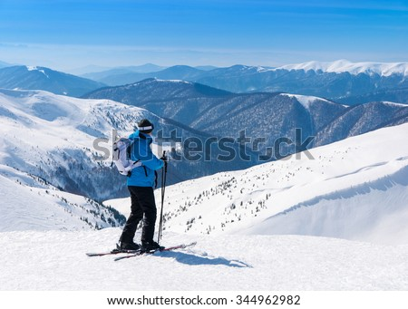 Skier in blue skisuit and alpine skis go skiing in snowy mountains landscape at ski resort - stock photo