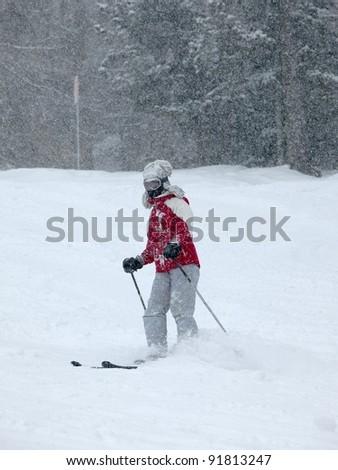 Skier in heavy snowfall - stock photo