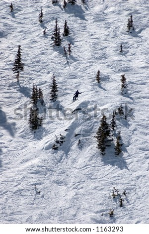 skier in midair on steep slope between small conifers - stock photo