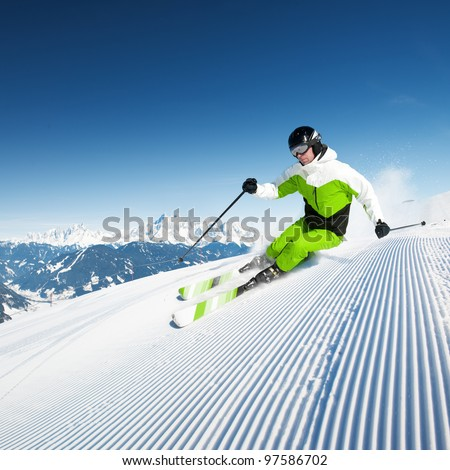 Skier in mountains, prepared piste and sunny day - stock photo