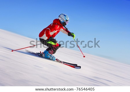 Skier in red jacket riding on hill. Motion blurred snow and clear blue sky - stock photo