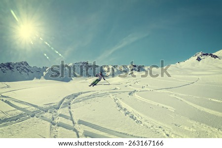 Skier is cruising through sunlit flat slope with deep snow. Filtered version with slight appearance of view through snow goggles. Snow capped mountains in the background.