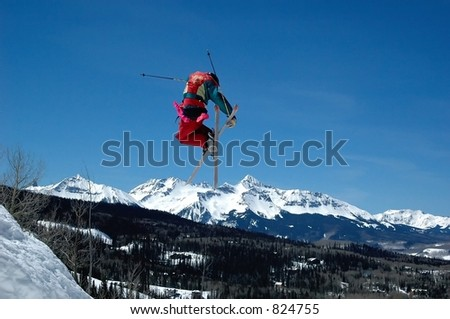 skier jumping doing stunt with snowy peaks in background - stock photo