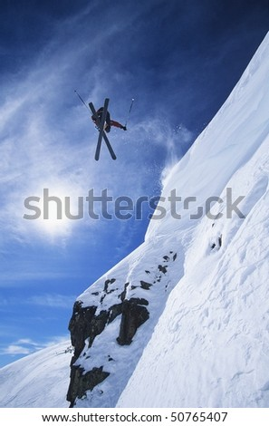 Skier jumping from mountain ledge - stock photo