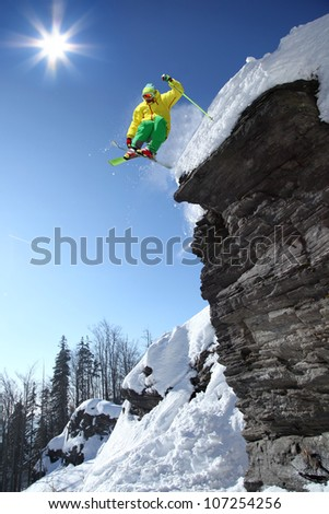 Skier jumping from the rock in high mountains - stock photo
