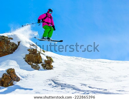 Skier jumping off a cliff against the blue sky in the mountains on a sunny day