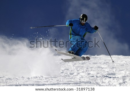 Skier jumping on a slope against blue sky. - stock photo