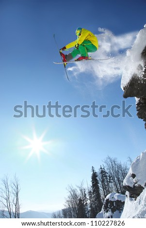 Skier jumping though the air from the cliff - stock photo