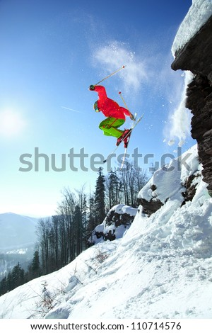 Skier jumping though the air from the cliff in high mountains - stock photo