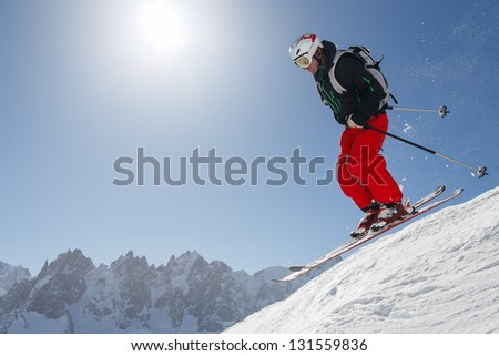 Skier jumping with the Mont Blanc massif in the background.