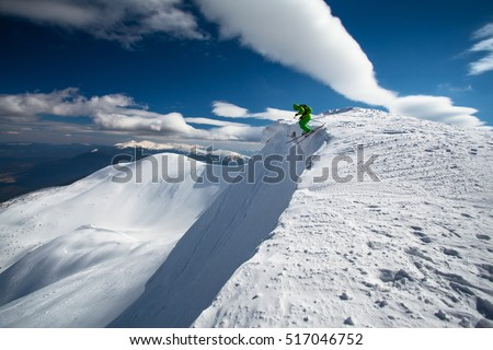 Skier jumps off mountain peak in powder snow, extreme drop. Skiing in winter Carpathian mountains. Hoverla mountain on background.