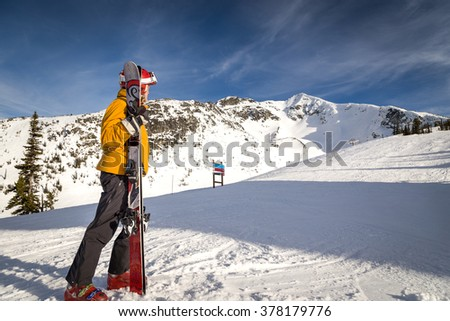 Skier looks towards a mountain peak.  - stock photo