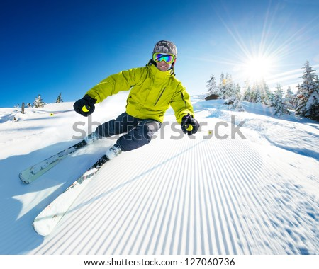 Skier on piste in high mountains - stock photo