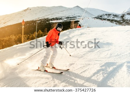 Skier on the slope in the mountains. Girl skiing on a sunny day - stock photo