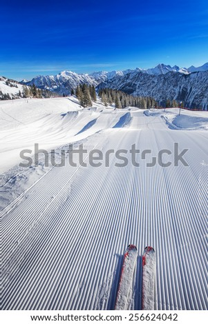 Skier ready to go skiing on the Ski slopes with the corduroy pattern on the top of Fellhorn Ski resort, Bavarian Alps, Oberstdorf, Germany - stock photo