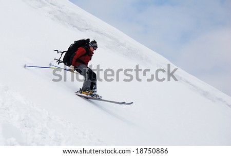 Skier running down the slope - stock photo