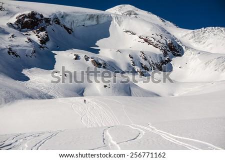 Skier running off-piste free ride slope at Elbrus (Caucasus, Russia) - stock photo