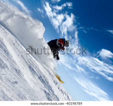 skier rush in clouds of snow powder against a blue sky - stock photo