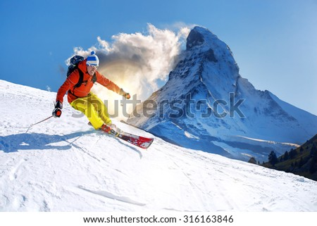 Skier skiing downhill against Matterhorn peak in  Switzerland - stock photo