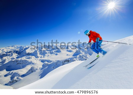 Skier skiing downhill in high mountains in fresh powder snow. Snow mountain range in background. Mt Fort Peak Alps region Switzerland.